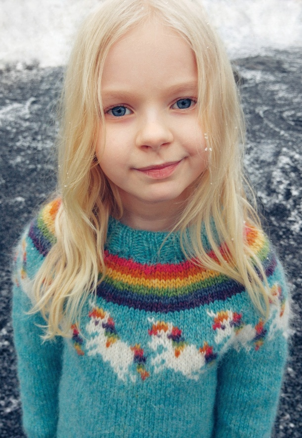 Girl wearing a rainbow unicorn knitted sweater. The pattern is available on Ravelry.com.